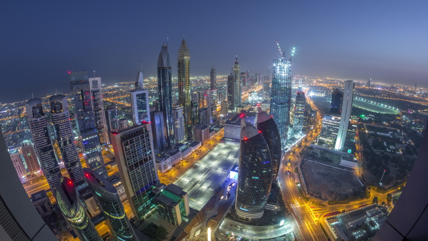 Skyline of the buildings near Sheikh Zayed Road and DIFC aerial night to day transition timelapse in Dubai, UAE. Modern towers and illuminated skyscrapers in financial center and downtown before #1034785919