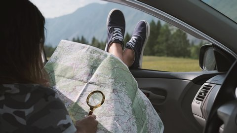 Girl tourist looks at a map using a magnifier while sitting in a car and sticking his legs out the window against the backdrop of the mountains