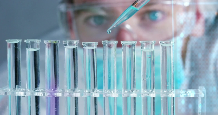 in a futuristic laboratory a scientist with a pipette analyzes a colored liquid to extract the DNA and molecules in the test. #1034827589