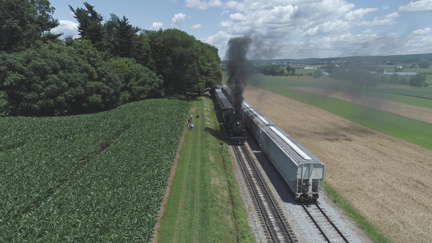 Aerial View of Farmlands and Countryside with a Vintage Steam Train Puffing up to Start up on a Sunny Summer Day