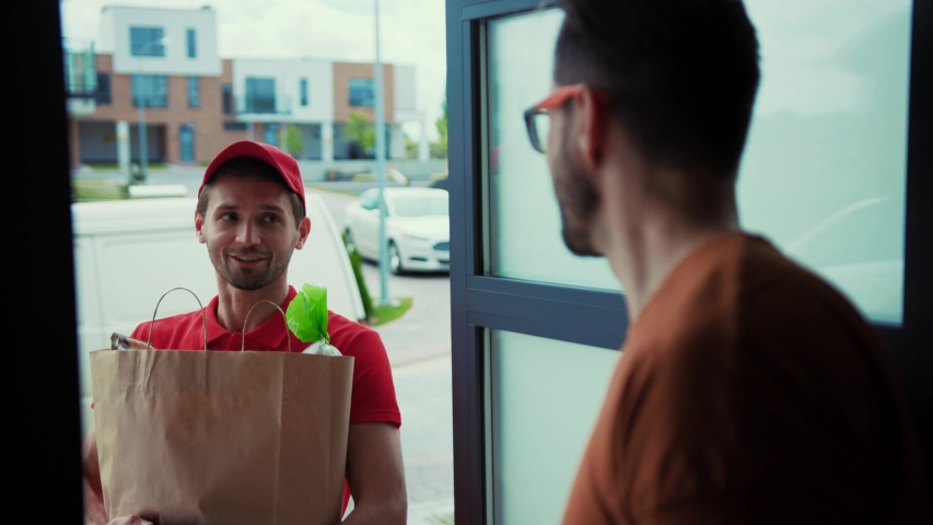 Convenient home food delivery. Side view of happy courier delivering food from supermarket. Male customer receiving food bag paying for order with credit card.