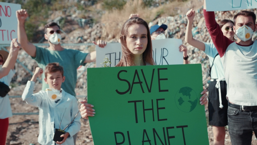 Environmental pollution problem. Group of inspired activists shouting at protest advocate green politics and clean nature. Young woman with agitative poster Save the Planet. #1034925839