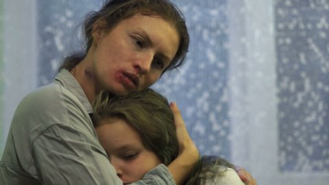 Teenage girl with bruises on her face cries in the arms of her mother. Domestic Violence, Children's Rights, Eastern Europe