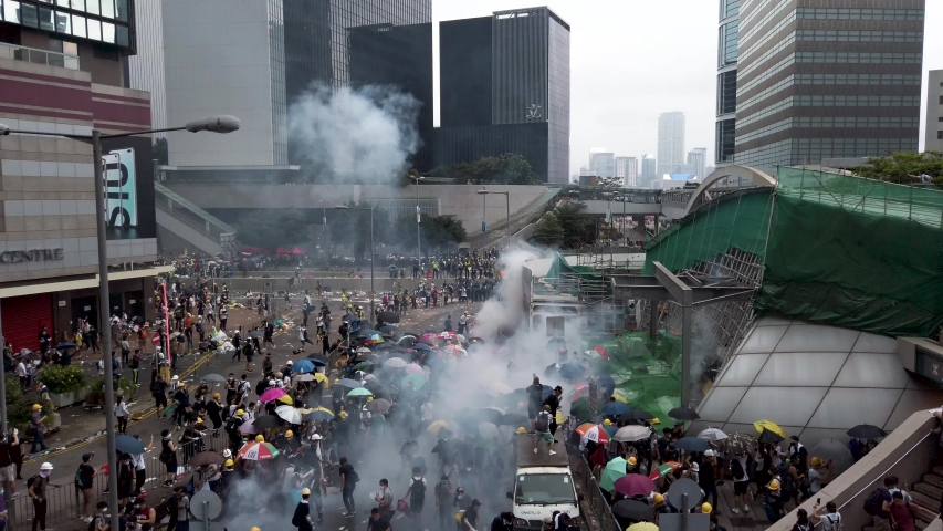 The Hong Kong protest against the extradition law. The riot police release tear gas to disperse the protesters | Shutterstock HD Video #1035043589