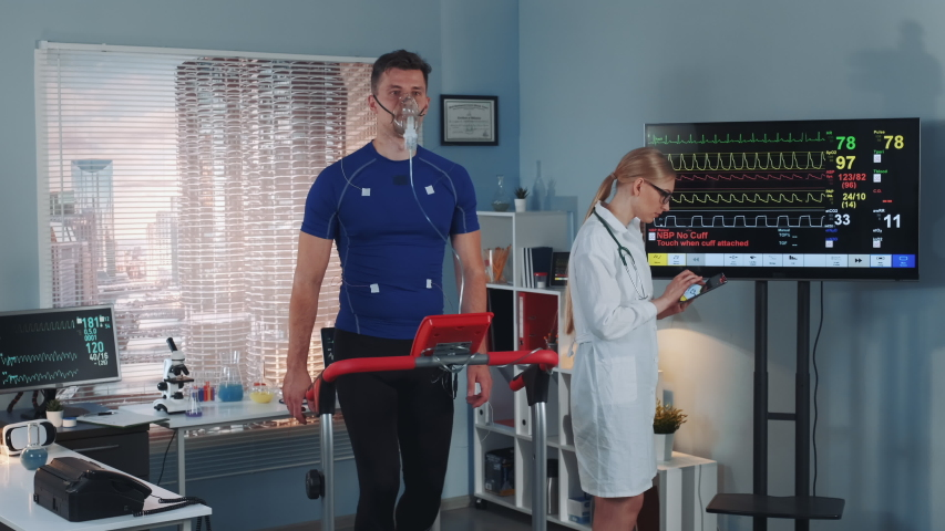 Sports Laboratory: Cardio respiratory test: cardiologist with tablet monitoring athlete EKG on display while the man in oxygen mask walking on treadmill. Showing on Laboratory Monitors. | Shutterstock HD Video #1035098729