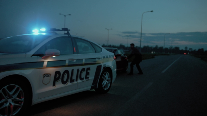 View of policemen stopping the lawbreaking sports car on the road. Scene of two cops arresting a drunk driver for high speed in the late evening. | Shutterstock HD Video #1035106409