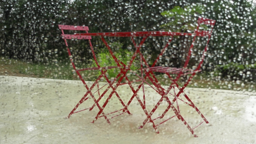 Rain drop on glass. POV veiw of garden through window with water drops in summer season. Metal table and chairs standing in yard | Shutterstock HD Video #1035171809