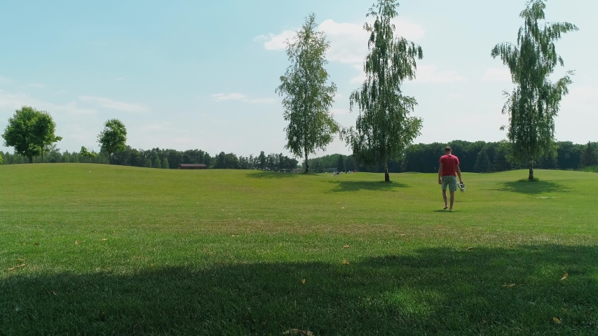 A man with a virtual reality headset in his hands walks along the green grass among the trees and turns to the camera. 4K drone footage.   Shutterstock HD Video #1035175859