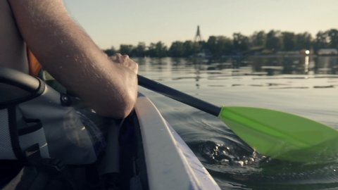 Paddle Rowing On A Quiet River At Sunset In Slow Motion.Kayak Oar Paddle Rowing In Sunrise,Backside Shot.Athlete Swimming On Canoe At Sunset Time On Tranquil River.Man In Life West Rowing On Lake.