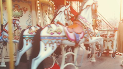 Traditional Vintage Carousel with Colorful Wooden Circus Horses. Merry-go-round in the Carnival Fair Park. Sunset soft light glow in the background. Entertainment, holidays, joy concept.