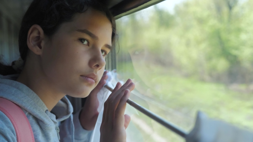 Little girl teenage is backpacker traveling by train. travel transportation railroad concept. tourist school girl in the train wagon with backpack lifestyle looking out the window waving his hand | Shutterstock HD Video #1035209729