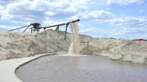 Industrial extraction of sand for construction. From the pipe discarded sand with water under strong pressure.