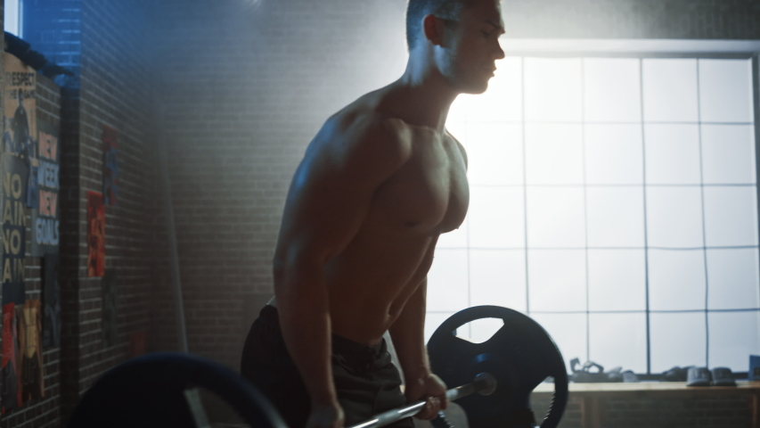 Arc Shot: Handsome Muscular Man Does Deadlift and Curls with a Heavy Barbell. Athletic Shirtless Man Training, Doing Power, Strength and Endurance Exercises with Barbell. Workout in the Hardcore Gym