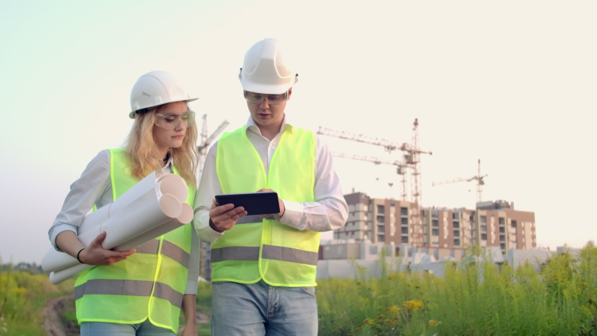 Engineer and controller go to the construction site on the background of cranes and talk about work. Discussion with the contractor on the construction progress | Shutterstock HD Video #1035355319