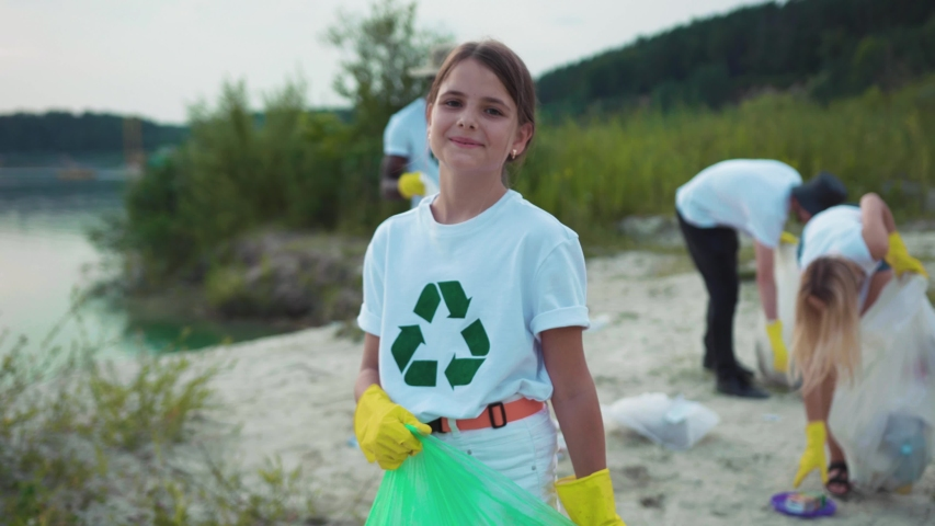 Porrtrait of little cute cheerful girl cleaning the sandy beach from garbage smiling of joy having good time outdoor. Young volunteer team on eco-friendly movement. | Shutterstock HD Video #1035365459