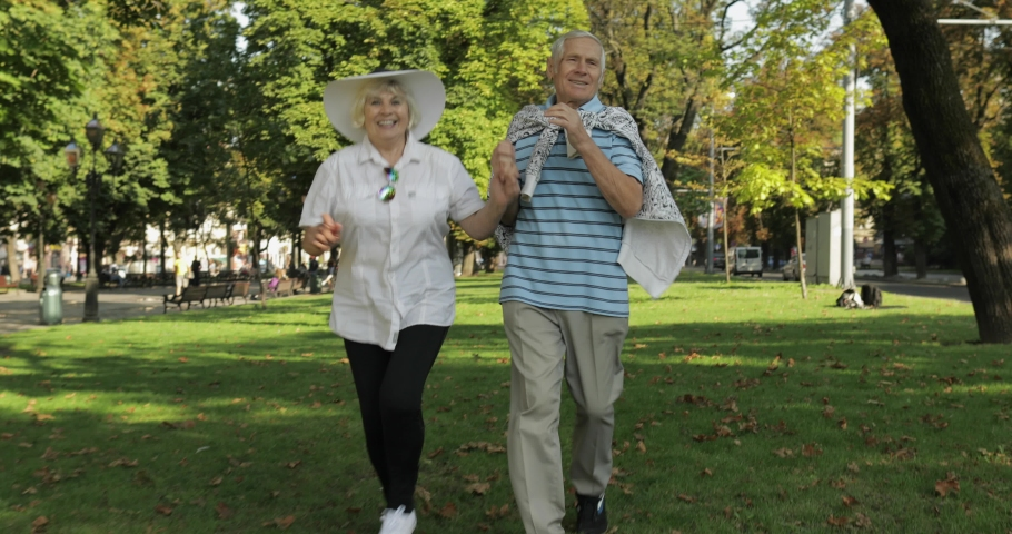 Senior happy two male and female tourists running and bouncing in town center park. Traveling in Lviv, Ukraine. Elegant woman in hat and handsome man in blue t-shirt. Family vacation concept | Shutterstock HD Video #1035377699