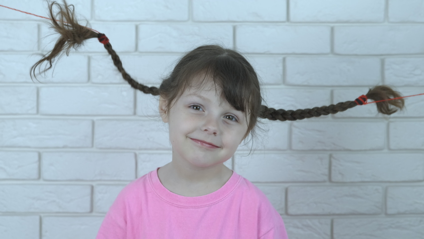 Funny kid with pigtails. Portrait of a beautiful little girl with dancing pigtails. | Shutterstock HD Video #1035394379