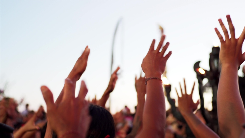 Indonesian men's hands in the air. They perform traditional Kecak dance which storyline is taken from Ramayana Hindu epic. Colorful beast on the stage. Uluwatu temple, evening   Shutterstock HD Video #1035482519