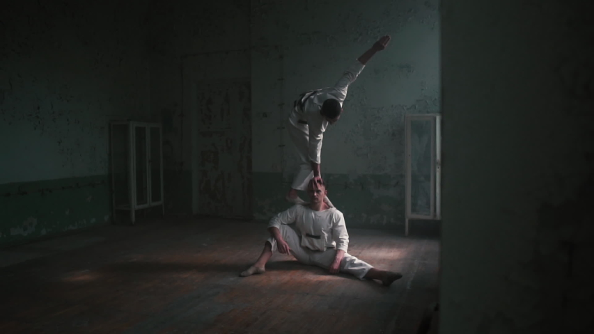 One man sitting and the second doing handstand with straddle split in slo-mo | Shutterstock HD Video #1035495689