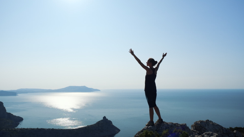 Young inspired woman raises her hands up standing on the top of a mountain above the sea against beautiful blue sky. Silhouette of a happy hiker woman standing on the summit. | Shutterstock HD Video #1035506279