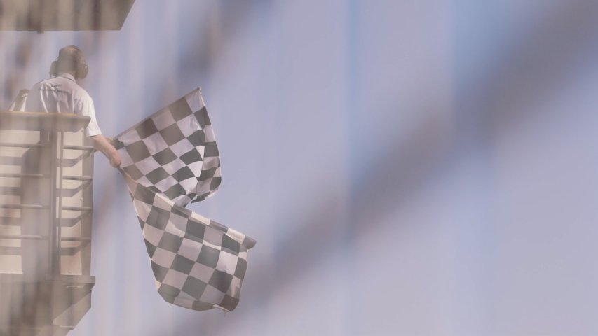 Man waving checkered race flag in slow motion at finish line on a raceway | Shutterstock HD Video #1035506819