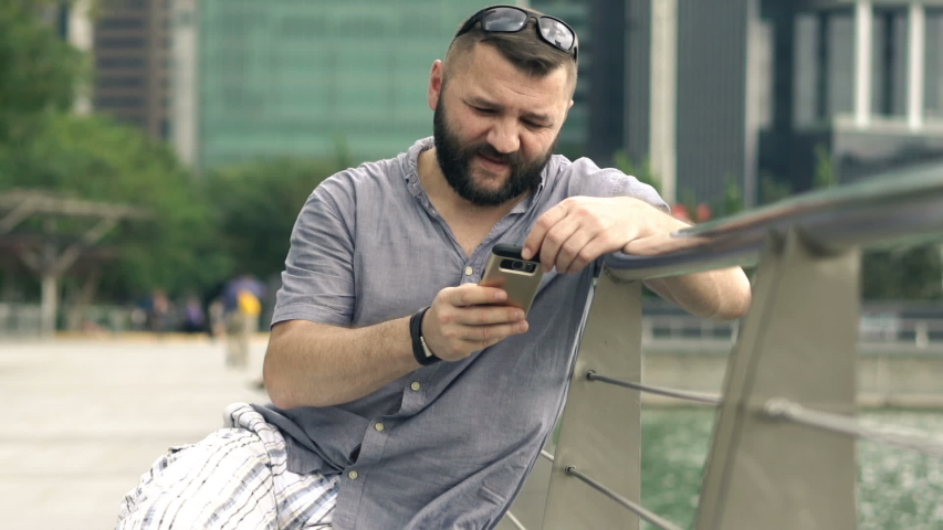 Young man texting, sending sms on smartphone in the city | Shutterstock HD Video #1035507839