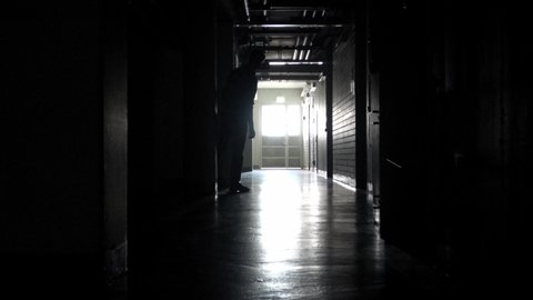 Someone watching behind pole in dark corridor  unknown person running fast  and hiding in darkness  useful for halloween, scary or creepy movies