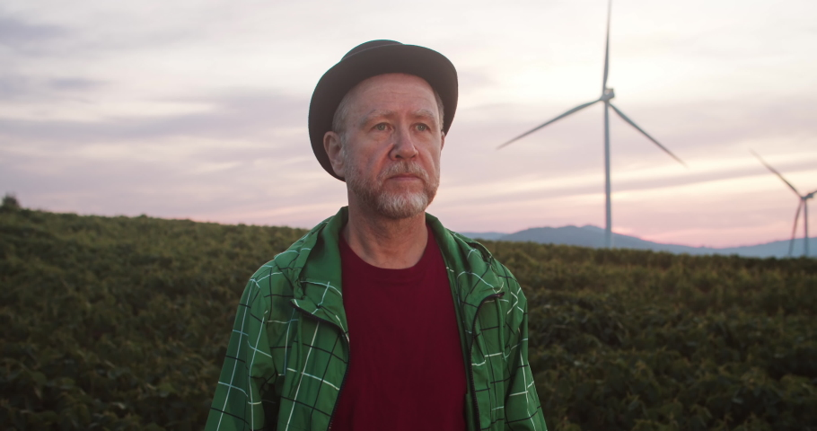 Outdoor portrait of attractive man in black hat looking at glorious rural fields landscape with wind turbines spinning in pink sunset lights.   Shutterstock HD Video #1035557609