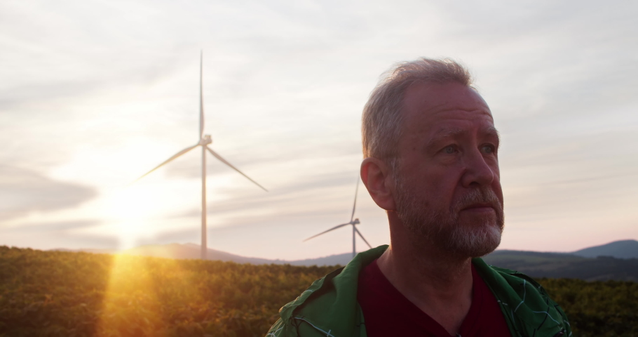 Portrait of handsome farmer staying in rural farmland smiling outdoor at sunset. Modern eco wind turbines spinning generating power on background.   Shutterstock HD Video #1035557639