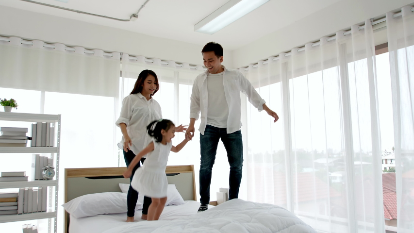 Asian family happy in the house. Father, mother and daughter aged three are jump, dance on the bed. Happiness in the home. Slow motion | Shutterstock HD Video #1035588839