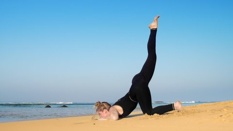 attractive young woman raises leg in yoga pose on endless blue ocean sand beach on sunny summer day low angle shot slow motion. Concept sport healthy lifestyle
