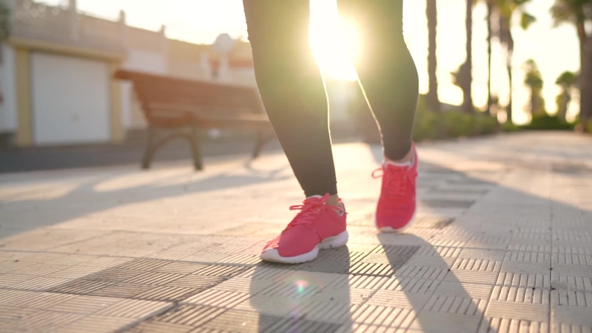 Close up of legs of a woman running along the palm avenue at sunset #1035610289