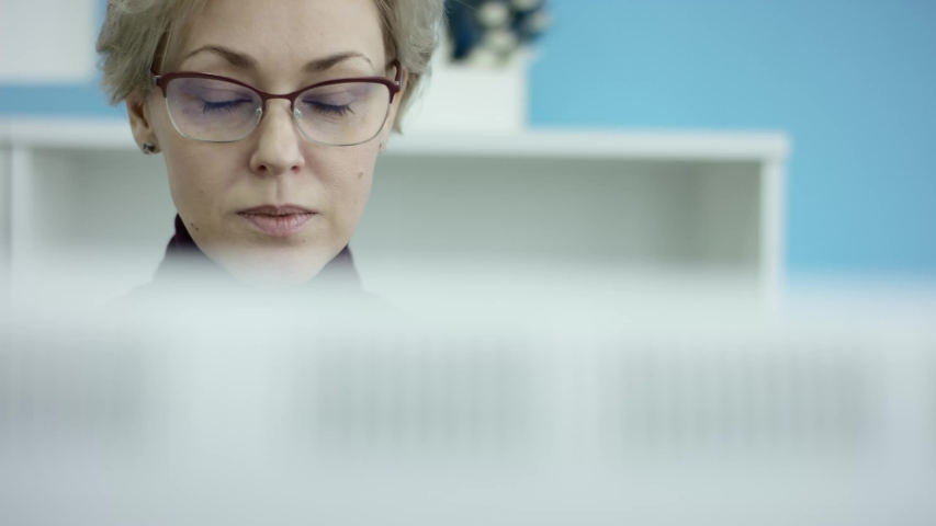 Stressed shocked angry young businesswoman in glasses annoyed about papers. She is reading and explored documents. She is an office worker. She is working in an modern office. She is sitting in an | Shutterstock HD Video #1035616169