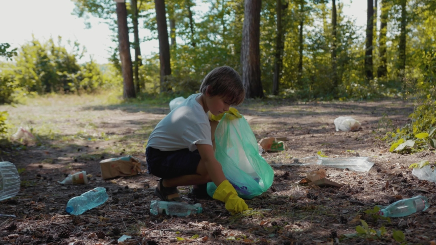 Close up voluteers activists child in gloves tidying up rubbish in park or forest save environment stop plastic pollution bag bottle recycle ecology garbage nature altruism care clean slow motion   Shutterstock HD Video #1035620009