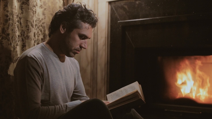 Young brutal man, reads a book by the fireplace in a country house, then closes the book, gets up and goes to bed | Shutterstock HD Video #1035629999