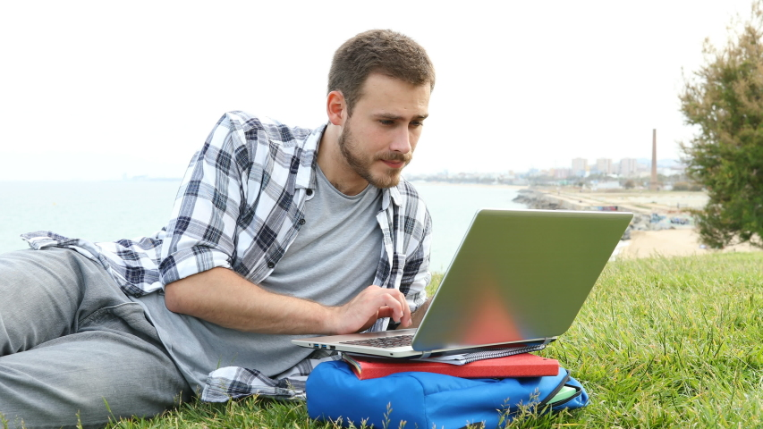 Surprised student using a laptop finds amazing online content lying on the grass | Shutterstock HD Video #1035636839
