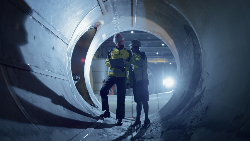 Two Heavy Industry Engineers Walking Inside Pipe, Use Laptop, Have Discussion, Checking Design. Construction of the Oil, Natural Gas and Biofuels Transport Pipeline. Industrial Manufacturing Factory | Shutterstock HD Video #1035704219