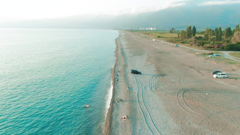 Aerial 4k top view of a beautiful tropical beach and sea waves. Flying over the sandy beach at sunset.