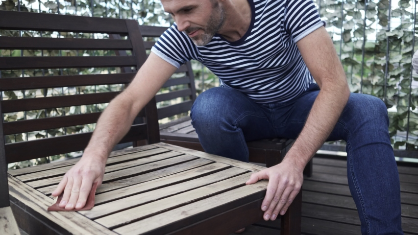 Panning shot of man sitting on apartment terrace sanding wooden garden chair | Shutterstock HD Video #1035832679