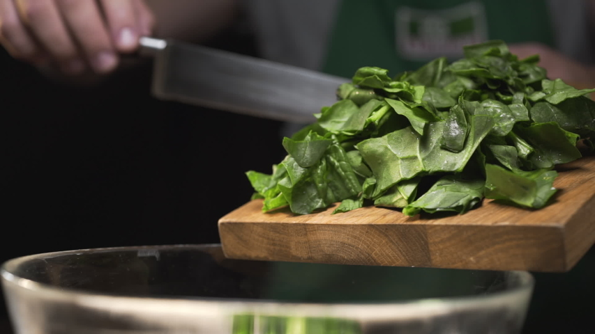 The cook pours chopped spinach from the cutting wooden board to the glass bowl, making the vegetable salad, cooking with greens, vitamin and healthy food, vegetarian meals, Full HD Prores 422 HQ | Shutterstock HD Video #1035892679