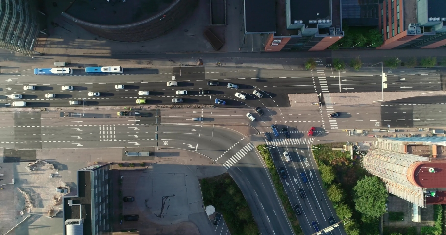 Aerial top down view of junction with cars and traffic at the morning rush hour during summer sunny day. Drone flying above from right to left filming straight down the street. Helsinki Finland | Shutterstock HD Video #1035923579