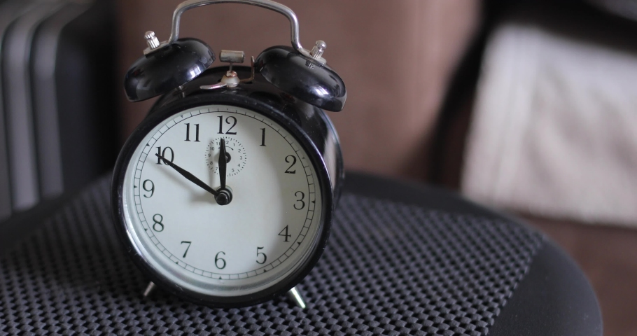 Man hitting an old fashioned alarm clock ringing early in the morning.
