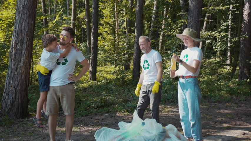 Smiling volunteers activists people in gloves tidying up rubbish environment concept stop plastic pollution bag bottle recycle ecology garbage nature altruism care clean slow motion | Shutterstock HD Video #1036040369