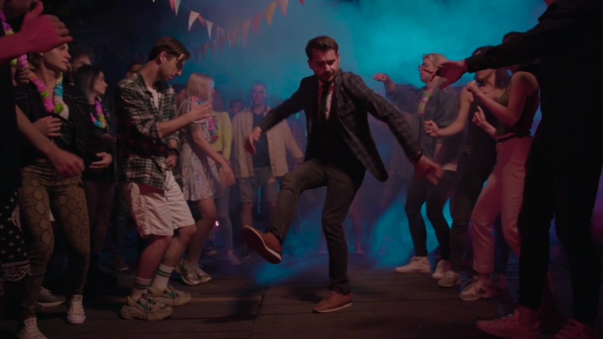 Modern businessman performing cool urban dance in front of delighted nice mood boys and girls dancing in neon lights in nightclub for entertainment. | Shutterstock HD Video #1036040669