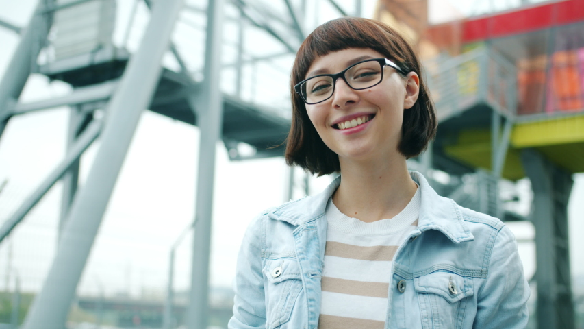 Slow motion portrait of beautiful girl in glasses touching hair smiling looking at camera outdoors standing alone against urban background. Millennials and emotions concept. | Shutterstock HD Video #1036086959
