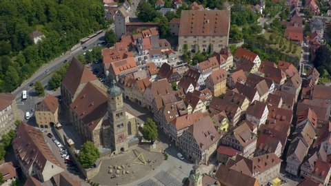 Aerial view of the city Schwäbisch Hall in Germany on a sunny day. Pan to the left above the city hall and church.