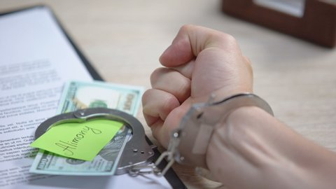 Male hand in cuffs and dollars with alimony sign on table, obligatory payment