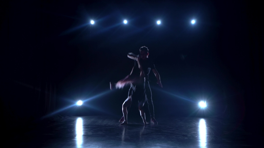 Young couple dancing contemp against black background with spotlights at studio. He doing support. | Shutterstock HD Video #1036149479