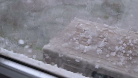 Hail Outside the Window. Hailstones fall on the air conditioner cover outside the window. Pieces of hail fall on the windowsill behind a plastic window. Natural phenomenon, cold rain with hail. Bad