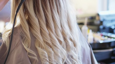 The hairdresser is making curls out of long white hair with professional hair curler for the women at the hair studio. A barber is holding hair iron close up and twisting strands, rear view..